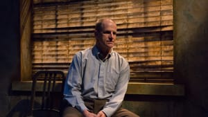 Anthony Lawton, wearing a button-down shirt, sits with a thoughtful look. Wooden blinds cast slats of light behind him.