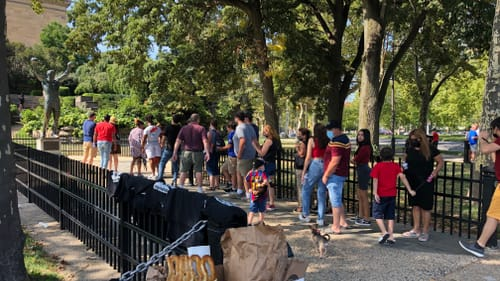 About 20 people stand in line to visit the Rocky Statue outside the museum. Pretzels, drinks, & shirts are for sale in front