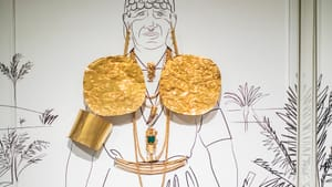 A life-size illustration of a Coclé man sports real-life bright gold plates, jewelry, belt, and armband.