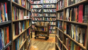 A photo from between two high bookshelves in The Strand, facing more bookshelves, and a rolling cart full of books.