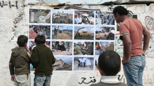 A photograph is never neutral: Residents of Bil'in examine an ActiveStills exhibit during a popular-struggle protest in the West Bank in July 2007. (Image courtesy of Slought.)