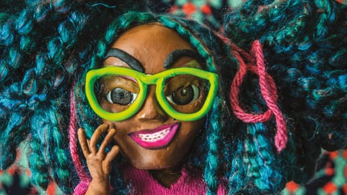 A stop animation still featuring a claymation woman with colorful hair, yellow framed glasses, and pink top.