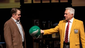 A Tommy and Me scene. Matt Pfeiffer as Didinger looks at a vintage Eagles helmet that Tom Teti as McDonald holds out to him