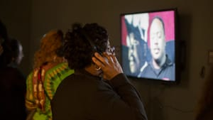 At the exhibition's opening reception, a viewer watches one of Scribe's videos. (Photo by Meredith Edlow)