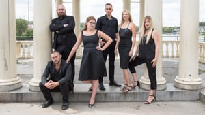 Six performers pose in front of gazebo pillars, dressed in all black.