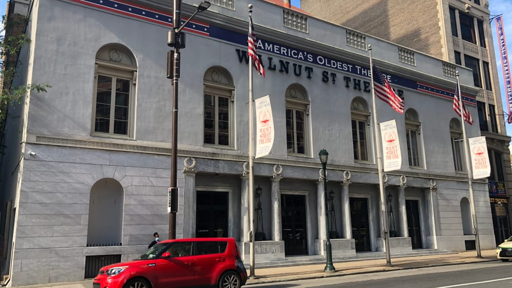 The Walnut Street Theatre today. It has a gray exterior with columns and large windows. American flags fly on poles in front