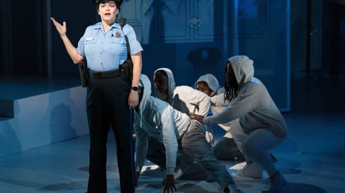 Mezzo-soprano Kirsten Chávez as Glenda Ramos, a West Philadelphia police officer who confronts the Family Stand, flanked by the hoodie-clad OGs. (Photo by Dominic M. Mercier.)