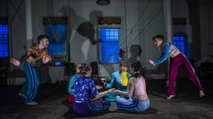 Four Wolfthicket dancers sit playing in a circle on the floor. On the sides, two standing dancers move with arms outstretched