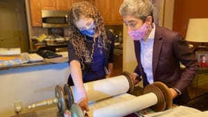 Renting a Torah actually isn't difficult, even in a pandemic: the author and her cousin, Scout, scan the parchment for the right chapter and verse. (Photo by Milt Spivack.)