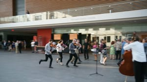Three violin players seem to be running and playing through a small crowd in what looks like a brightly lit museum space