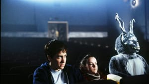 A young man, woman, and someone in a rabbit suit with a creepy bunny mask sit at an empty movie theater together.