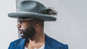 Garrett, a Black man, wears a blue denim blazer and white top with a wide-brim hat and glasses in a portrait-style photo.