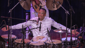 Martinez, an Afro-Cuban man, sits before congas, cymbals, and microphones, with his arms out, his mouth wide as he's sings.