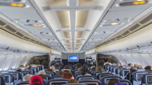 An inside view from the back of a commercial airplane, with the white cabin ceiling overhead and people in rows of seats.