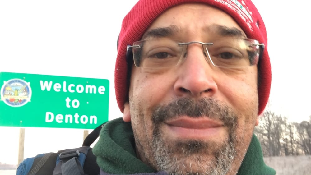 Johnston, a Black man, takes a selfie in front of a city limits sign that reads Welcome to Denton.