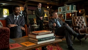 Three men dressed in black suits look towards someone or something off camera, in a densely wood-furnished room.