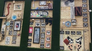 A wall with decorative artifacts and framed b&w illustrations of various insects populate a wall with its own grass frame.