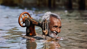 """""""Tailor Carries His Sewing Machine through Monsoon Waters"""" (Gujarat, 1983). (Photo © Steve McCurry)"""