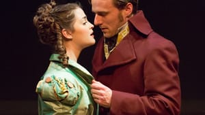 A woman and a man in lavish Regency costumes are coming close to kissing.