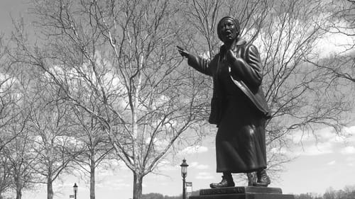A black and white photo of a statue of Harriet Tubman in a park.