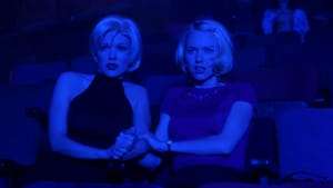 Two women with identical blonde bobcuts sit in a theater, slightly spooked, holding hands. The room is tinted an intense blue