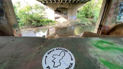 A white circular sticker with the words Walk Around Philadelphia sits on a concrete barrier by a small creek.