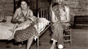 """Summer of 1936. William Edward """"Bud"""" Fields, wife Lily Rogers Fields, and infant daughter Lilian at their sharecropper cabin in Hale County, Alabama. Photograph by Walker Evans for the Farm Security Administration."""
